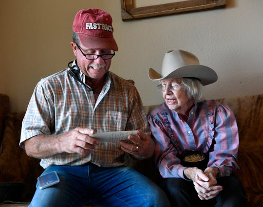 Mark Hadley looks at a photograph with his mother Virgina Reger August 29. Reger is a retired rodeo trick rider, saying what attracted her to it as a young girl were the glitzy garments other trick riders got to wear.