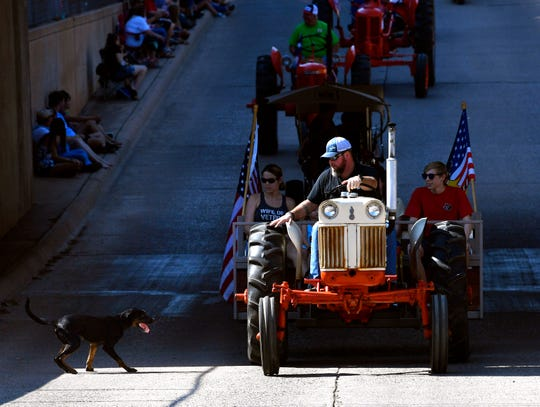 Tony Bray tries to warn a stray dog away from his tractor at the start of Saturday's West Texas Fair & Rodeo Parade . The dog escorted the tractor partway through the parade but had left by the time Bray came back to the Pine Street underpass.