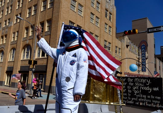 An astronaut waves to the crowd from the Discovery Center float during Saturday's West Texas Fair & Rodeo Parade.
