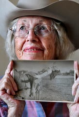 """Virginia Reger holds an undated photograph of her performing one of her trick riding stunts. Reger said she took a lot of falls over the years but never worried about them. """"It just happens,"""" she said."""
