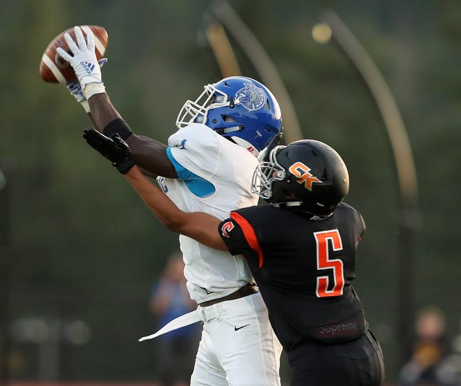 Olympic's Malcolm DeWalt intercepts a pass intended for Central Kitsap's Jason Almonte (5) during the first quarter of their game at Cougar Field on Friday, September 6, 2019.