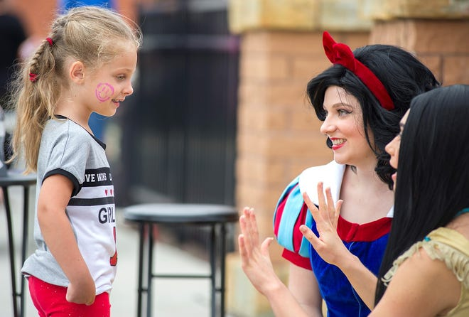 """The princesses greet a young fan outside Shines Art Park during Bucyrus First Friday. The theme of the September event was """"Harvest and History."""""""