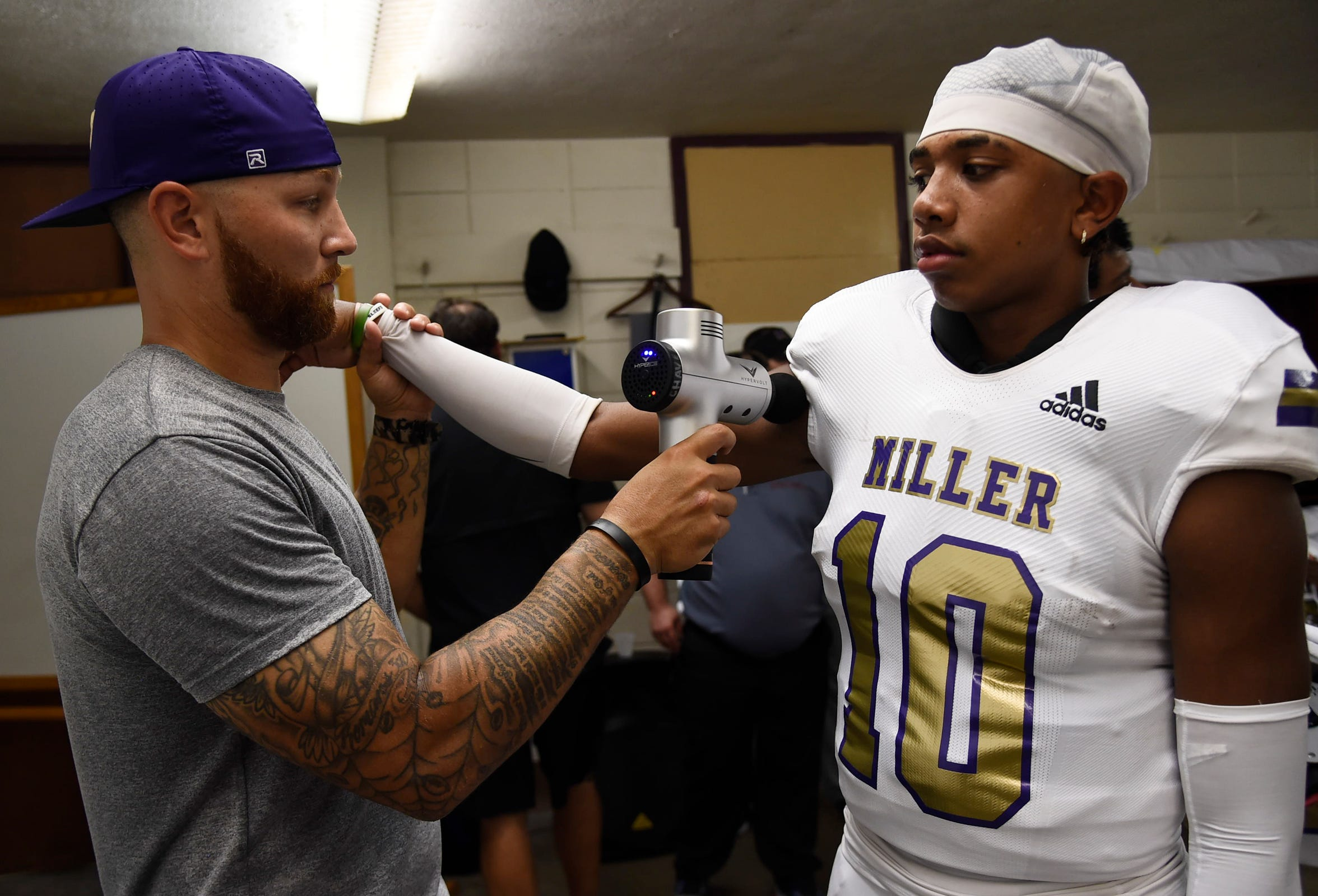 Miller's Passing Game Coordinator Bradly Chavez uses a massage tool for Andrew Body before their game against Sinton, Friday, Sept. 6, 2019, in Sinton. Miller won, 51-9.