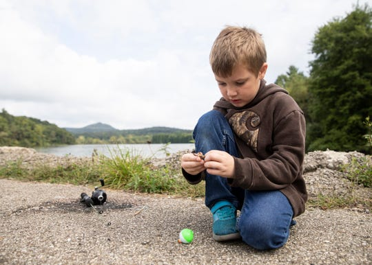Bentley McClarren, 6, attempts to bait his own hook on his own at a dock at the Ross Lake fishing at the Annual Family Fishing Day on September 7, 2019.