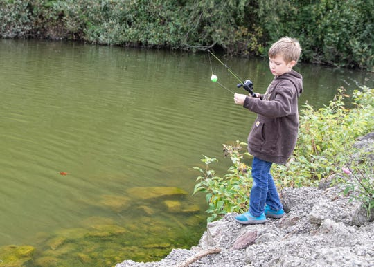 Bentley McClarren examines his line before casting it into the Ross Lake during the fourth annual Family Fishing Day.