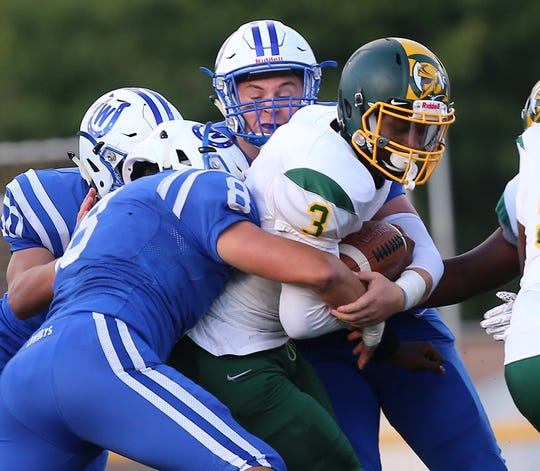 Taft quarterback Robert Brazziel is tackled by Wyoming defenders during their football game Friday, Sept. 6 , 2019.
