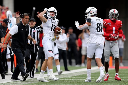 Cincinnati Bearcats head coach Luke Fickell, left, encourages Cincinnati Bearcats wide receiver Alec Pierce (12) after a reception for a first down in the first quarter of a college football game against the Ohio State Buckeyes, Saturday, Sept. 7, 2019, at Ohio Stadium in Columbus.