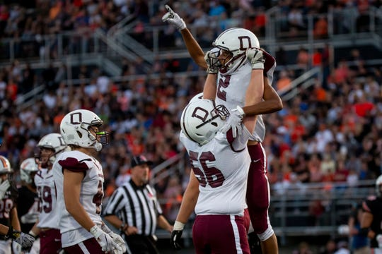 Dowling Catholic's Louis Brooks (2) is lifted up by Dowling Catholic's Joe Ryan (56) after he scored during their football game at Valley Stadium on Friday, Sept. 6, 2019 in Des Moines. Dowling Catholic takes a 14-9 lead over Valley into halftime