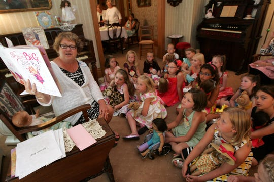 """Beth Haigh of Urbandale reads the book """"Dream Big Little Pig!"""" at a tea party for children in 2011 at the Olmsted-Urban House, 4010 70th St. in Urbandale."""