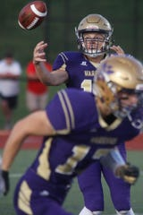 Norwalk quarterback Zachary Marker takes a wild snap in the Warriors' game against Dallas Center-Grimes on Sept. 6. Marker threw for 169 yards and ran for 86 in Friday's win over Pella.