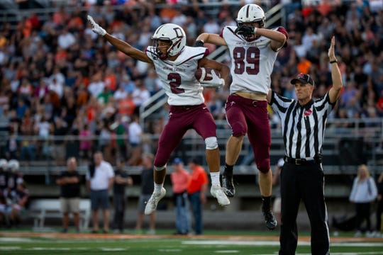 Dowling Catholic's Louis Brooks (2) and Dowling Catholic's Andrew Lentsch (89) celebrate a touchdown during their football game at Valley Stadium on Friday, Sept. 6, 2019 in Des Moines. Dowling Catholic takes a 14-9 lead over Valley into halftime