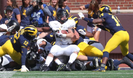 Michigan Wolverines defenders tackle Army Black Knights running back Connor Slomka (25) during first half action Saturday, September 7, 2019 at Michigan Stadium in Ann Arbor, Mich.