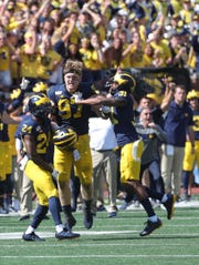 Michigan Wolverines' Lavert Hill (24) Aidan Hutchinson (97) and Vincent Gray (31) celebrate the 24-21 win against the Army Black Knights, Saturday. September 7, 2019 at Michigan Stadium.