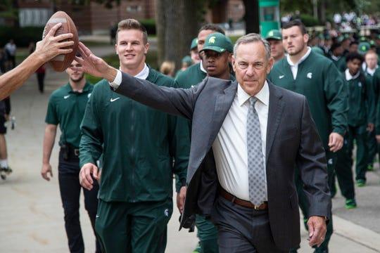 Michigan State head coach Mark Dantonio high-fives a fan as the team marches toward Spartan Stadium in East Lansing, Saturday, September 7, 2019.