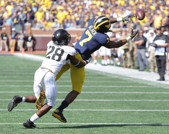 Michigan Wolverines wide receiver Tarik Black (7) is defended by Army Black Knights defensive back Jabari Moore (28) during second half action Saturday, September 7, 2019 at Michigan Stadium in Ann Arbor, Mich.