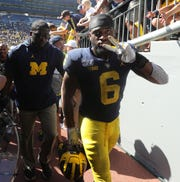 Josh Uche leaves the field after the 24-21 win.