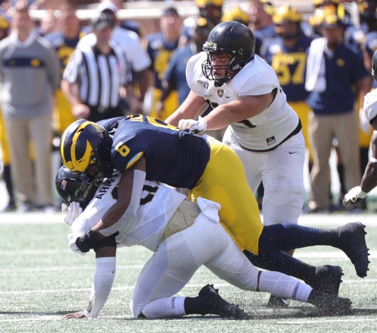 Michigan Wolverines linebacker Josh Uche tackles Army Black Knights' Kelvin Hopkins Jr. during the first half Saturday, September 7, 2019 at Michigan Stadium.