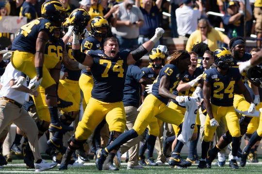 Michigan offensive lineman Ben Bredeson (74) and the rest of the Wolverines storm the field after winning the game in the second overtime.