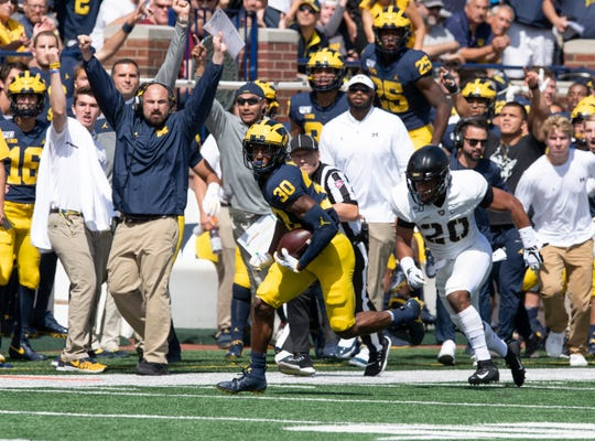 Michigan freshman Daxton Hill picks up a first down on a fake punt-pass play, which led to Michigan's first touchdown in the first quarter.