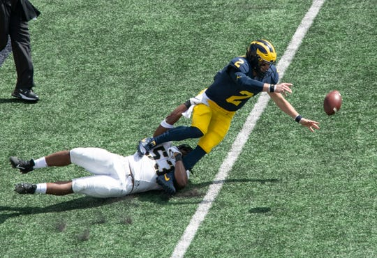 Quarterback Shea Patterson fumbles for a turnover during Michigan's first possession of the game.