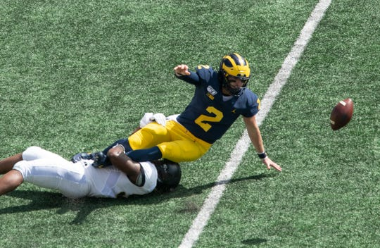 Michigan quarterback Shea Patterson fumbles the the ball for a turnover as he is tackled by Army linebacker Arik Smith first quarter. It was the first of two fumbles in the first quarter by Patterson.
