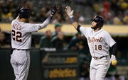 Detroit Tigers' Dawel Lugo, right, celebrates with Victor Reyes (22) after scoring against the Oakland Athletics in the 11th inning. The Tigers won 5-4.