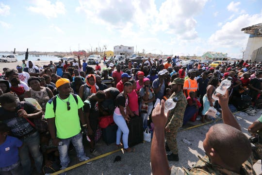 A Bahama's Army officer delivers water to the people evacuated prior boarding a ferry to Nassau at the Port in Marsh Harbor, Abaco Island, Bahamas, Saturday, Sept. 7, 2019.
