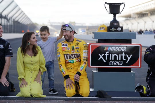 NASCAR Xfinity Series driver Kyle Busch celebrates with his wife, Samantha, and son, Brexton, after winning the NASCAR Xfinity auto race Saturday at the Indianapolis Motor Speedway.