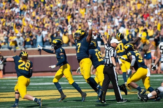 Michigan defensive players Jordan Glasgow (29), Ambry Thomas (1), Khaleke Hudson (7), Kwity Paye (19) and Jordan Anthony (34) celebrate a fumble recovery in the second overtime to seal the 24-21 victory.