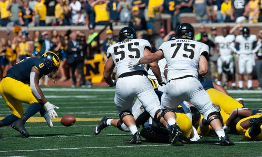 Michigan linebacker Josh Uche (6) scoops up a fumble by Army quarterback Kelvin Hopkins Jr. in the second overtime to end the game.