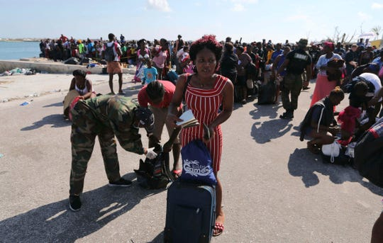 A Bahama's Army officer registers the people prior boarding a ferry to Nassau at the Port in Marsh Harbor, Abaco Island, Bahamas, Saturday, Sept. 7, 2019.