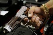 A customer looks at a SIG Sauer hand gun at a Jan. 9, 2016, gun show in Miami.