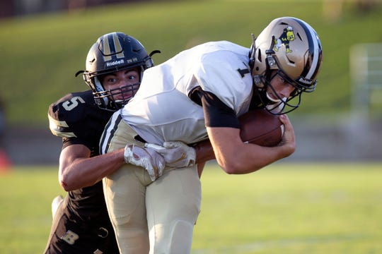 Jasper's Nathan Rillo carries the ball while attempting to escape from Boonville's Devin Mockobee during Friday's game at Bennett Field in Boonville. Jasper defeated Boonville 35-0. Traci Westcott/The Herald