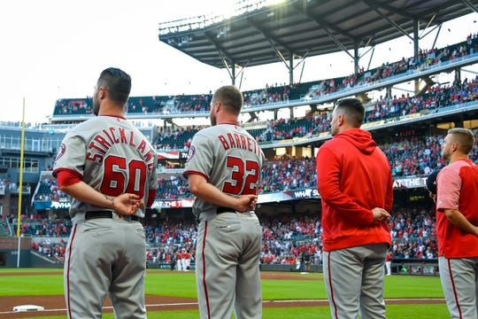Washington Nationals pitcher Aaron Barrett (32) stands with his teammates for the national anthem before a baseball game against the Atlanta Braves in Atlanta, Ga., Friday, Sept. 6, 2019. Barrett, from Evansville, Ind., was brought up from the AA Harrisburg Senators and it is the first time in the MLB in four years (he didn't play baseball for two of those) after working his way back from surgeries for injuries.