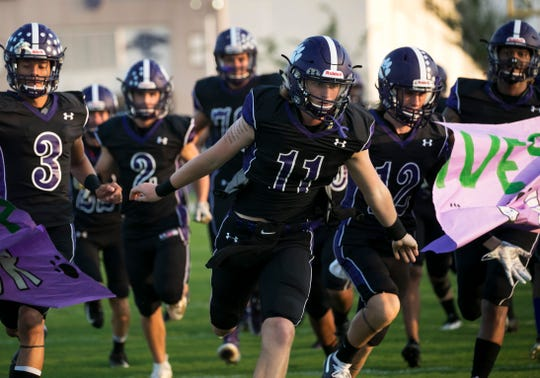 Cypress Lake quarterback C.J. Shedd leads the team onto the field for their game against Fort Myers on Friday, September 6, 2019, at Cypress Lake High School.
