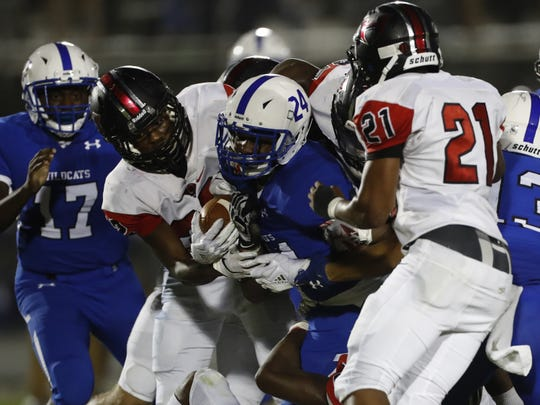 Woodmont's Jeremiah Massey( 24) is swarmed by Hillcrest defenders during Friday night's game at Woodmont High in Piedmont.