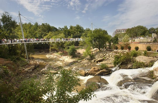 The first visitors to the Reedy Falls Liberty Bridge make their way over Reedy River Falls Friday after an opening ceremony featuring the designers and dignitaries responsible for the bridge. 9/10/04