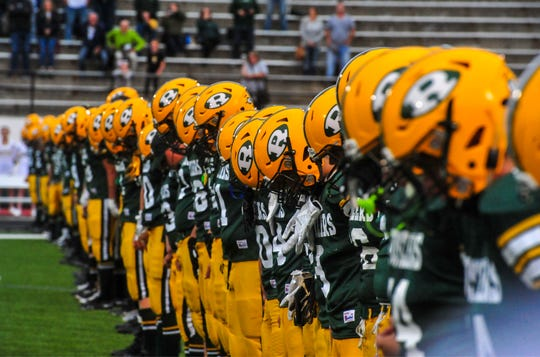 The CMR football team bows their head during a moment of silence for their teammate David Delcomte on Friday night before their game against Butte.