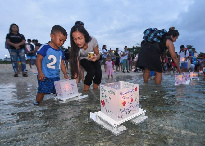 Ceremony attendees place their proa lantern in the waters of Tumon Bay for the Guam Nikkei Association's fifth annual Lantern Floating Ceremony at the Gov. Joseph Flores Beach Park in Tumon, Sept. 7, 2019.