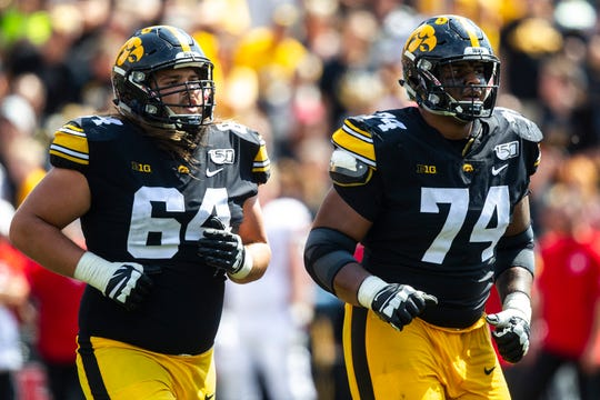 Iowa's new starting right guard Kyler Schott (64) runs to the sideline alongside good friend Tristan Wirfs in a Sept. 7 win over Rutgers. Hawkeye offensive line coach Tim Polasek said Wednesday that Schott, a walk-on, will continue to battle Cole Banwart to see who starts week-by-week.