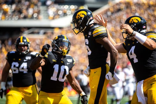 Iowa wide receiver Ihmir Smith-Marsette (6) gets embraced by teammates Mekhi Sargent (10) and Nate Stanley (4) after catching a touchdown pass during a NCAA Big Ten Conference football game against Rutgers, Saturday, Sept. 7, 2019, at Kinnick Stadium in Iowa City, Iowa.