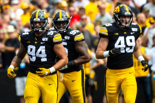 Iowa's A.J. Epenesa, from left, Cedrick Lattimore and Nick Niemann celebrate after a stop during a NCAA Big Ten Conference football game against Rutgers, Saturday, Sept. 7, 2019, at Kinnick Stadium in Iowa City, Iowa.