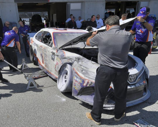 Denny Hamlin's crew inspects the crash damage from a late Brickyard 400 practice tire problem on Sept. 7, 2019 at the Indianapolis Motor Speedway.