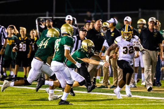 Bettendorf's Harrison Bey-Buie (32) gets tackled by Iowa City West's Kalen Haworth (24) during a Class 4A varsity football game, Friday, Sept. 6, 2019, at Trojan Field in Iowa City, Iowa.