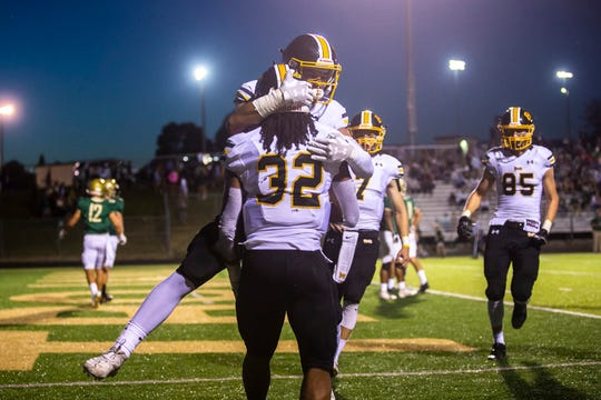 Bettendorf's Harrison Bey-Buie (32) gets embraced by teammate Tynan Numkena after scoring a touchdown during a Class 4A varsity football game, Friday, Sept. 6, 2019, at Trojan Field in Iowa City, Iowa.