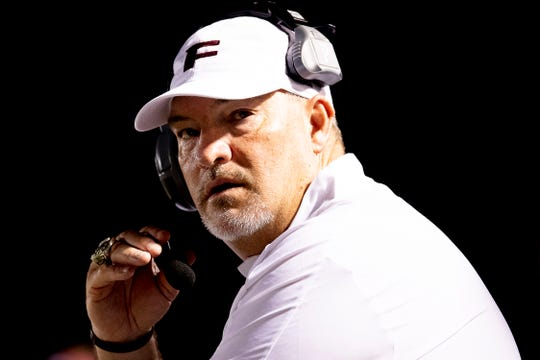 Fulton Head Coach Rob Black eyes the scoreboard during a football game between Fulton and Powell at Fulton High School in Knoxville, Tennessee on Friday, September 6, 2019.