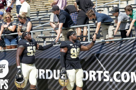 Purdue defensive lineman KJ Stokes (59) and Purdue defensive lineman Lawrence Johnson (90) greet fans as they walk off the field after defeating Vanderbilt, 42-24, Saturday, Sept. 7, 2019 at Ross-Ade Stadium in West Lafayette.