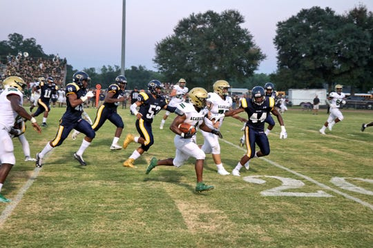 Acadiana High running back (1) Dillan Monette runs the ball past the Carencro High defenders Friday, Sept. 6, 2019.