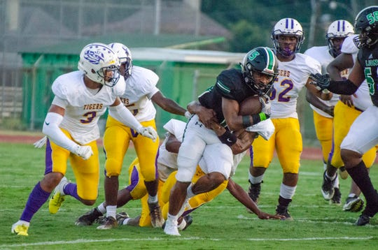 Lafayette High's Derezz Landry gets taken down by Jeanerette High defenders Friday, Sept. 6, 2019.