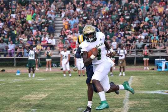 """Acadiana High running back Jeremiah """"Lucky"""" Brooks runs the ball past a Carencro High defender Friday, Sept. 6, 2019."""